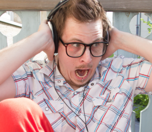 man with headphones annoyed by loud sound