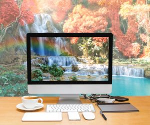 Conceptual image of a workspace with computer desktop on Beautiful waterfall with soft focus and rainbow in the forest