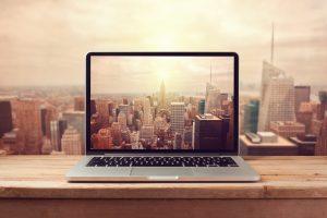 Laptop computer over New York city skyline.