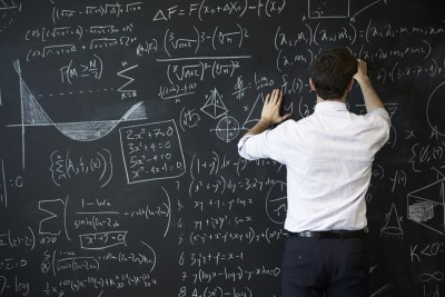 man writing formulas on a chalk board