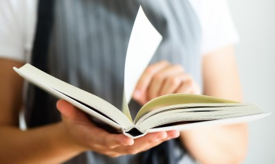An open story book, with a page being turned by the reader.