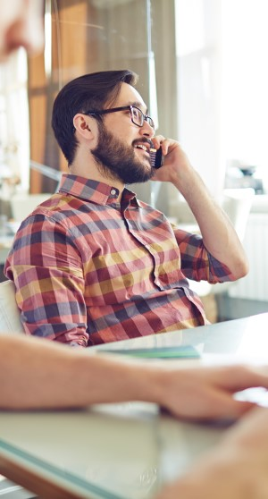 An image of a young, bearded professional on the phone. Probably calling a client to provide fantastic customer service while reminding them of a payment deadline coming up.