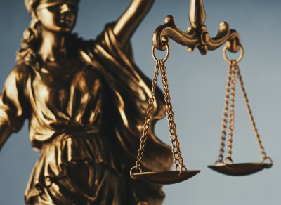 Image of a golden cast of Justice, blindfolded and holding her scales aloft, with the scales being the focal point.