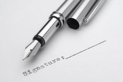 An uncapped fountain pen sitting on top of a contract awaiting a signature. Legally, that signature means everything.