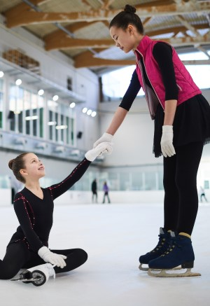 Two adolescent girls in ice skates. One is taking the other's hand to help her up after a fall.