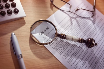 Contract lying on desk with a magnifying glass emphasizing the word 'contract'. The importance of a signed contract in client work cannot be overstated.