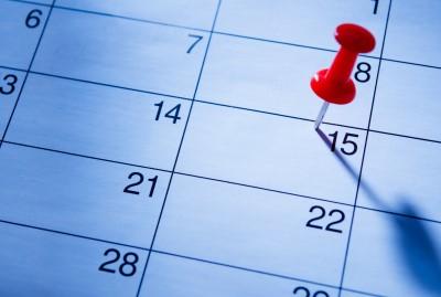 Red pin marking a date in a calendar.