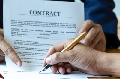 Image of a contract being signed. Your client's signature on the contract and scope of work represents that they are aware of any consequences that you hold the right to enforce.