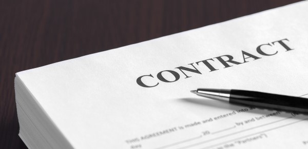 Close-up image of a contract. Don't do anything without the client signing one.